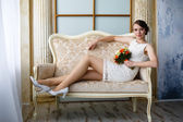 young beautiful sexy woman with flowers in a chair on a couch — Foto de Stock