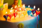 Happy birthday written in lit candles on colorful background — Stock Photo