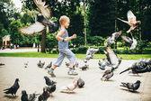 Мальчик играет с голубями птиц в парке Гомель, Беларусь — Стоковое фото