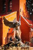 Statue Of Archangel Michael near Red Catholic Church Of St. Simo — Stock Photo