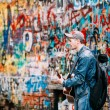 Постер, плакат: Man sings music band KINO songs near Viktor Tsoi Wall in Moscow Russia