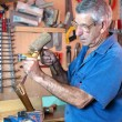 Man working carving wood with a chisel and hammer — Stock Photo #59804671