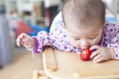 Baby girl eats at the high chair — Stock Photo