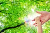 The parent's hand holds on one year old baby's hand behide the nature green tree and blur light close up — Stock Photo