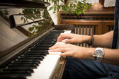 Male hands playing piano indoors — Stock Photo