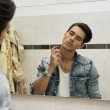 Handsome young man in bathroom, spraying cologne or perfume — Stock Photo #53322629