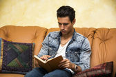 Handsome young man reading book at home, sitting on couch — Stock Photo