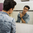 Handsome young man in bathroom, spraying cologne or perfume — Stock Photo #53485719