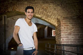 Handsome young man in old building smiling — Stock Photo