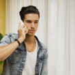 Handsome young man talking on telephone at home — Stock Photo #54202751