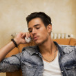 Handsome young man talking on telephone at home — Stock Photo #54202967