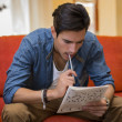 Young man sitting doing a crossword puzzle — Stock Photo #54246905