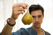 Young man holding a ripe yellow pear — Stock Photo