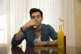 Young man sitting drinking alone — Stock Photo