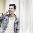 Handsome young man talking on telephone at home smiling — Stock Photo #54466783