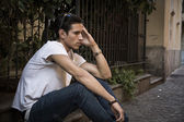Sad, unhappy young man outdoor, sitting on pavement — Stockfoto