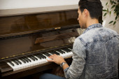Young handsome male artist playing classical upright piano — Stock Photo