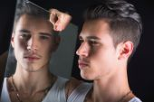 Narcissistic handsome young man admiring his reflection in mirror — Foto de Stock