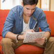Young man sitting doing a crossword puzzle — Stock Photo #54507817