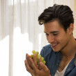 Young man holding a ripe bunch of grapes — Stock Photo #54508063