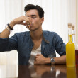 Young man sitting drinking alone at a table with two bottles of liquor — Stock Photo #54508345