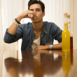 Young man sitting drinking alone at a table with two bottles of liquor — Stock Photo #54508357