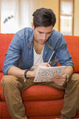 Young man sitting doing a crossword puzzle — Stock Photo