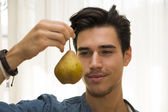 Young man holding a large ripe yellow pear — Stock Photo