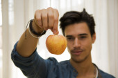 Young man holding a large delicious ripe apple — Stock Photo