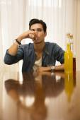 Young man sitting drinking alone at a table with two bottles of liquor — Stock Photo
