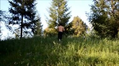 Young man in danger running away up and then down a hill — Stockvideo
