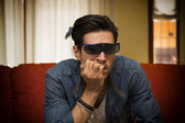 Young man wearing 3d glasses sitting watching a video — Stock fotografie