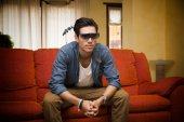 Young man in 3d glasses sitting watching television — Stock fotografie