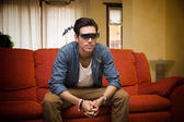Young man in 3d glasses sitting watching television — Stock Photo
