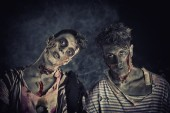 Two male zombies standing on black smoky background — Stock Photo