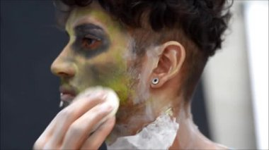 Young male actor or performer applying zombie make-up on his face — Stockvideo