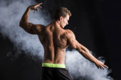 Handsome shirtless bodybuilder striking a pose, back view — Стоковое фото