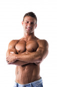 Smiling shirtless muscular young man standing with arms crossed — Stock Photo
