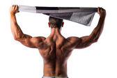 Back of shirtless muscular hunk holding towel above his head — Stock Photo