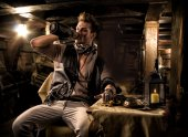 Pirate Drinking from Bottle in Ship Quarters — Stock Photo