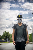 Young man wearing white creepy mask outdoor in city street — Stock Photo