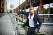 Handsome muscular blond man standing in city environment — Stockfoto