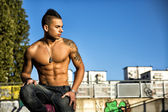 Handsome fit athletic shirtless young man in city setting — Stock Photo