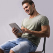 Muscular young man sitting on chair while reading from e-book device with happy expression — Stock Photo #60260587