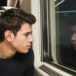 Young man travelling in train looking out of window — Stock Photo #60263803