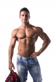 Shirtless muscular young man holding backpack in his hand — Stock Photo
