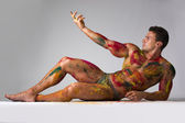 Muscular young man with skin painted with Holi colors, laying down on the floor — Stock Photo