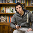 Attractive young man sitting listening to music — Stock Photo #61322523