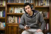 Attractive young man sitting listening to music — Stock Photo
