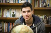 Handsome young man holding a globe indoors — Stockfoto